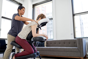 Chinese woman massage therapist giving a neck and back pressure