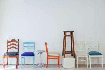 lots of multicolored chairs in the interior of the white room