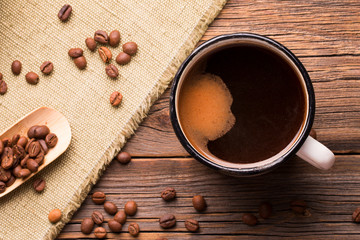 Coffee mug and coffee beans on a wooden background. Vintage iron mug filled with hot freshly brewed coffee.