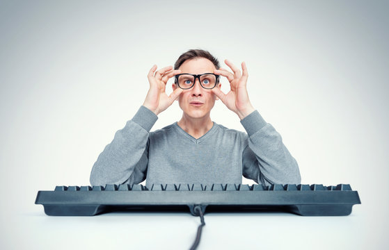 Funny man holds glasses in his hands while sitting at a keyboard in front of a computer