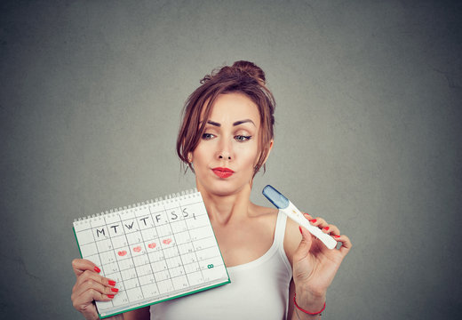 Doubtful woman holding positive pregnancy test and her periods calendar
