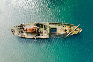 Shipwreck of old wooden ship in turquoise water at sea coast, top down aerial view. Vityaz Bay, Primorsky Krai, Far East, Russia