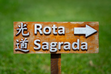 Placa de madeira sinalizando a direção da rota sagrada próxima ao templo japonês. Escrito em japonês e português