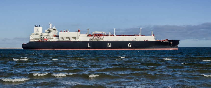 SWINOUJSCIE, WEST POMERANIAN / POLAND - 2019: LNG tanker with gas cargo maneuvers at port wharf for mooring at the gas terminal