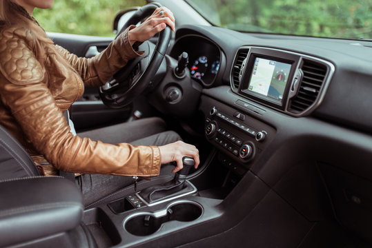 woman in summer autumn, driving car, parking reversing, engages automatic transmission. Start movement of car, inclusion of parking mode. Leather jacket, touch screen.interior of car.