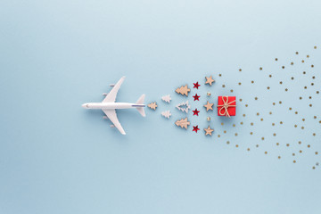 Poster Airplane Christmas composition. Airplane flying in sky star gift bauble set top view background with copy space for your text. Flat lay.