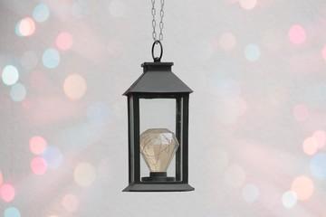 Schwarze Laterne mit LED - Glühbirne hängend, abstrakt happiness