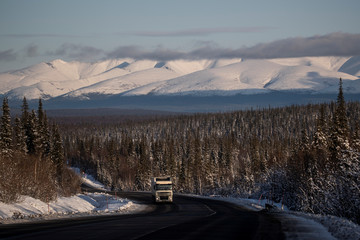 A truck drives along a road with snow covered Khibiny mountains in the background in Murmansk region