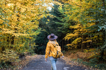 Woman with backpack and hat walking on dirt road in autumn forest