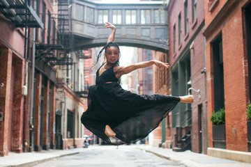 Dancer facing forward mid leap above ground