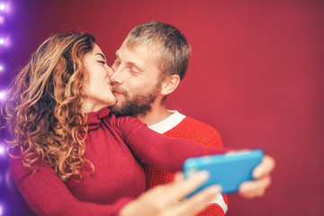Happy couple taking selfie with mobile smartphone camera - Young romantic lovers kissing and celebrating Christmas holidays - Love relationship, xmas and technology trends concept