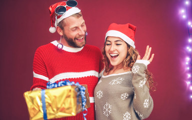 Happy couple celebrating Christmas time sharing presents - Young people having fun during x-mas holidays - Xmas vacation and traditional culture lifestyle concept
