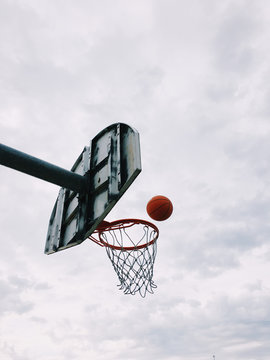Low angle view of basketball falling through hoop