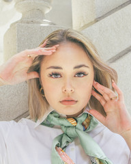 Portrait of young woman posing with hands on her face