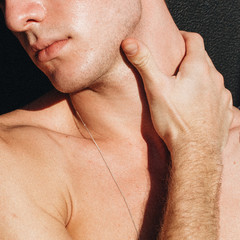 Close up view of young man holding his neck