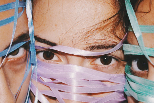 Close up of three women with faces covered with satin ribbons