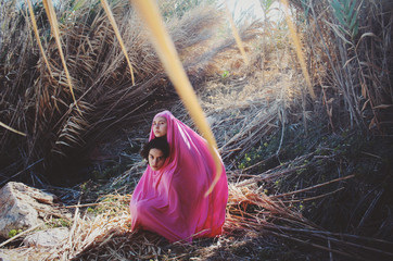 Portrait of two women covered in single pink cloth near haystack