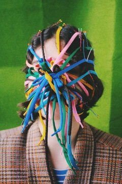 Womans face covered with colorful shoelaces
