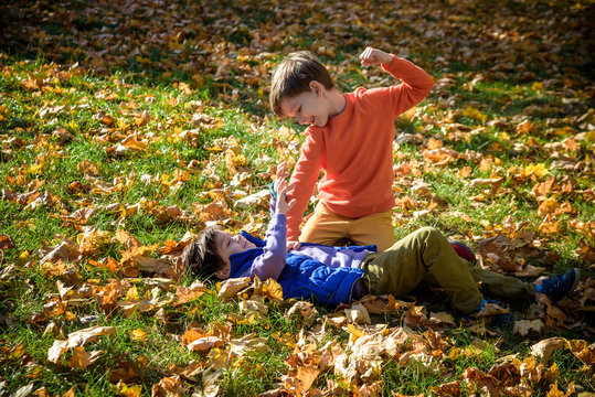 Two boys fighting outdoors. Friends wrestling in summer park. Siblings rivalry. Aggressive kid hold younger boy on ground, try to hit him