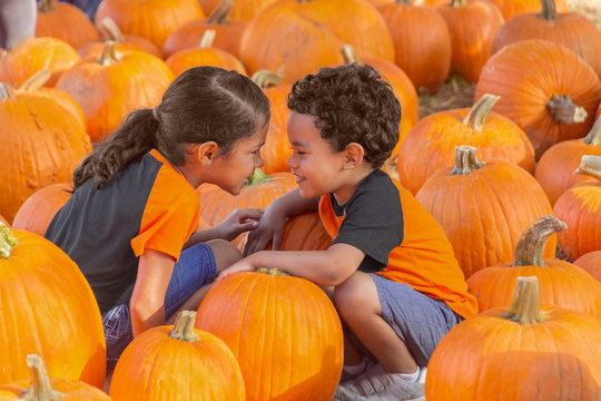 The small boy attempts to blend in down low with the pumpkins while his sister gets in his face to distract him. Both kids are right in the middle of the pumpkin patch playing.