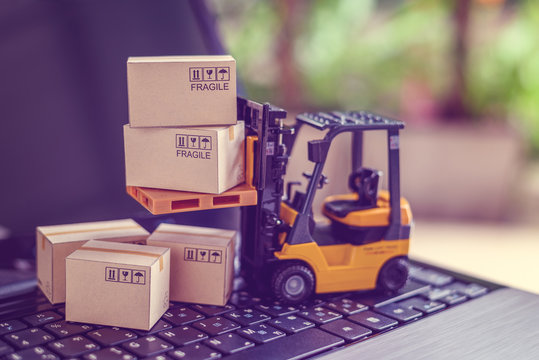 Logistics, supply chain and delivery service concept : Fork-lift truck moves a pallet with box carton. Boxes on a laptop computer, depicts wide spread of products around globe in ecommerce booming era