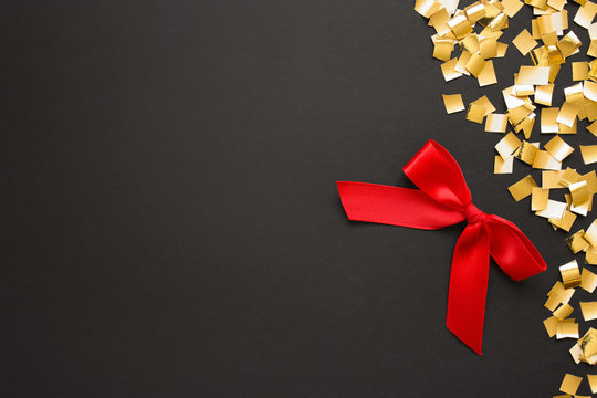 Red gift bow with golden confetti on black backgound