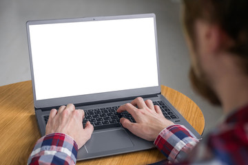 Mockup image: man typing on laptop computer keyboard with white blank screen on wooden table in home interior. Mock up, copyspace, freelance workspace, template, entertainment and technology concept