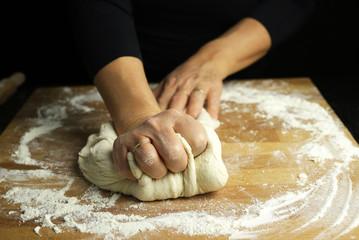 Preparare la tradizionale pasta fatta in casa. Primo piano delle mani della donna che impastano pasta fresca per produrre pane o pizza su una tavola infarinata