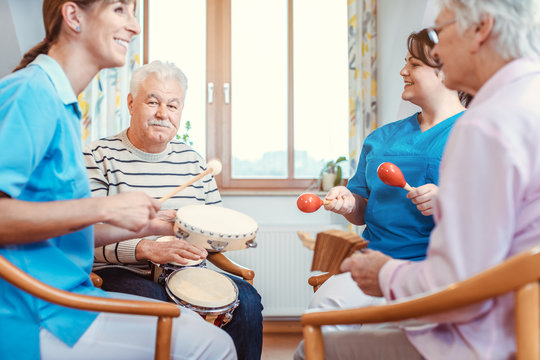 Seniors in nursing home making music with rhythm instruments