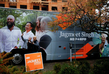 Supporters take a photo next to the campaign bus of NDP leader Jagmeet Singh at the NDP election office on Election Day in Burnaby