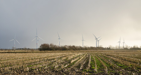 Wind turbines creating electricity out of wind energy on stubble field in rural Germany.