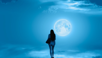 """Beautiful woman walks on the clouds and Night sky with full moon """"Elements of this image furnished by NASA"""