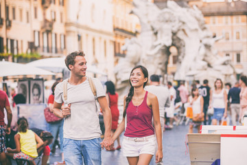 Wall Mural - Rome travel young couple tourists walking in city streets on Navona Square sightseeing in Italy. Asian girl holding hands with Caucasian boyfriend happy, tourism lifestyle.