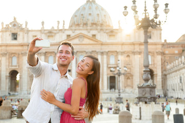 Wall Mural - Europe luxuy travel vacation tourists in Rome, Italy. Honeymoon vacation couple taking selfie photo with phone at Vatican city St Peter's Basilica church at sunset. Summer holiday cruise destination.