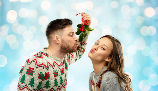 christmas, people and holiday traditions concept - portrait of happy couple in ugly sweaters kissing under mistletoe over festive lights on blue background