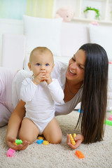 happy mother with her baby playing with a baby toys on the floor
