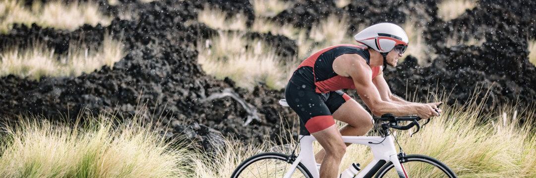 Biking triathlete man cycling road bike under the rain during triathlon race in Hawaii nature landscape. Sport athlete training endurance workout extreme weather banner panoramic.
