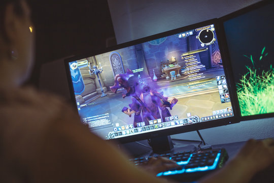 WROCLAW, POLAND -  SEPTEMBER 04th, 2018: Woman playing World of Warcraft: Battle of Azeroth game. WoW is a massively multiplayer online role-playing game released in 2004