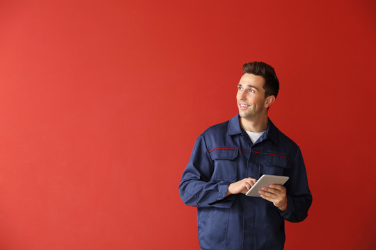 Male car mechanic with tablet computer on color background