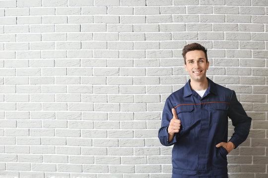 Male car mechanic showing thumb-up near brick wall