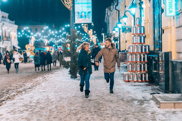 Young adult couple walking on snow covered sidewalk