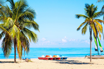 The tropical beach of Varadero in Cuba with sailboats and palm trees on a summer day with turquoise...