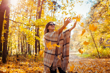 Fall season activities. Woman throwing leaves in autumn forest. Young woman having fun outdoors