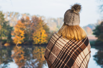 Woman with blanket and knit hat with pom-pom enjoying cold misty morning at lake