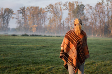 Woman with blanket enjoying tranquil scene at foggy morning at nature