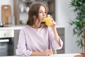 Papiers peints Jus, Sirop Beautiful young woman drinking orange juice in kitchen