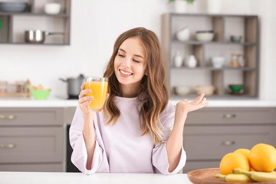 Beautiful young woman drinking orange juice in kitchen