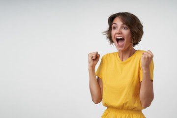 Attractive brunette lady with short brown hair being wild with joy while cheering for her favorite team, raising fists and screaming happily, posing over white background