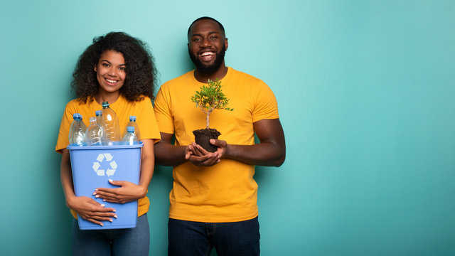 Happy couple hold a plastic container and a small tree over a light blue color. Concept of forestation, ecology, conservation, recycling and sustainability