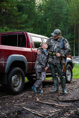 Happy hunter with his son near their pickup truck before hunting in a forest